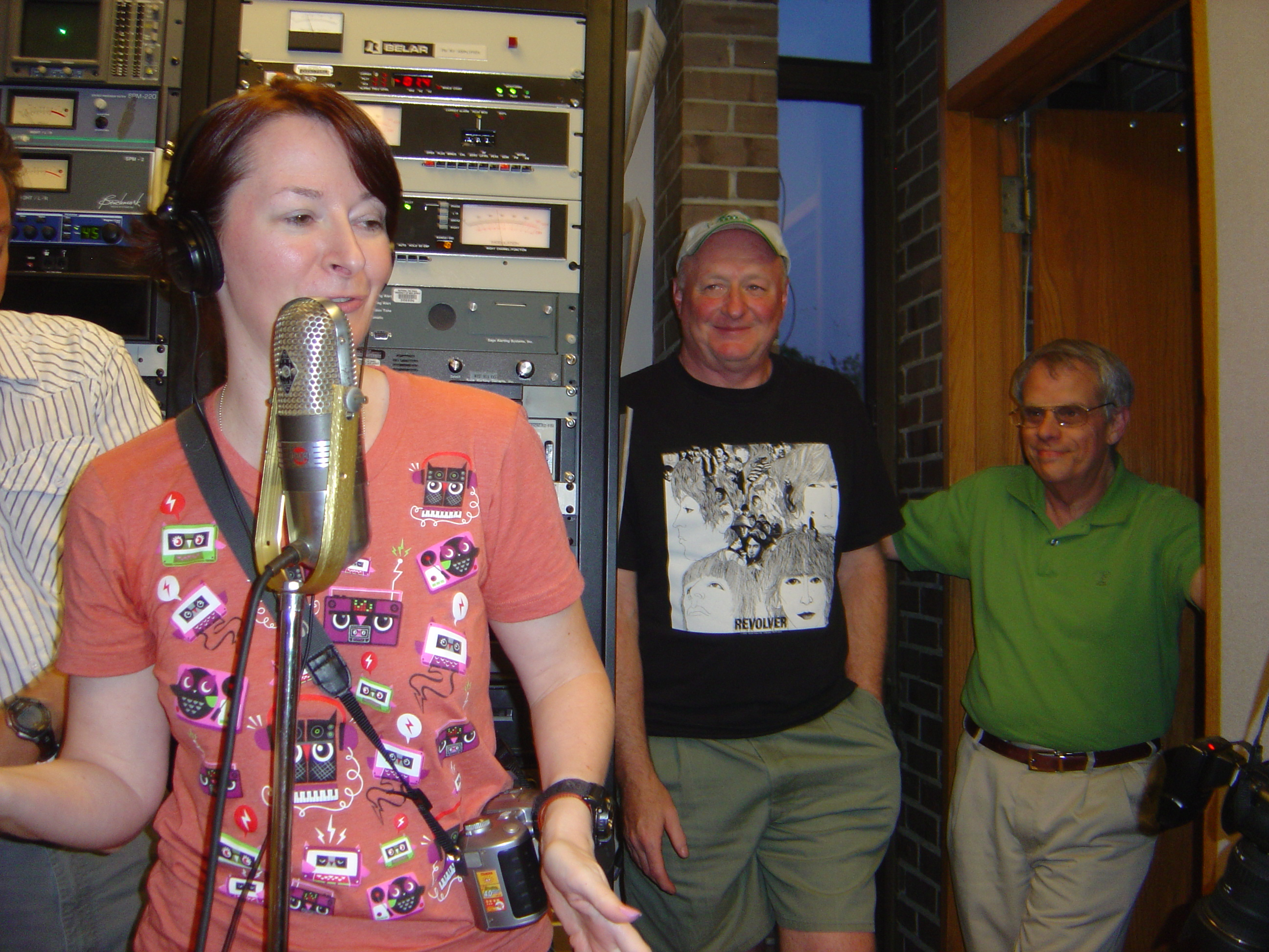 Lisa Uber at the microphone, John Cooper and Tim Espar look on.